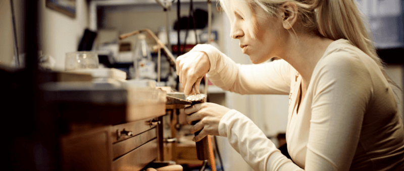 Female bench jeweller using a file on a jewellery item