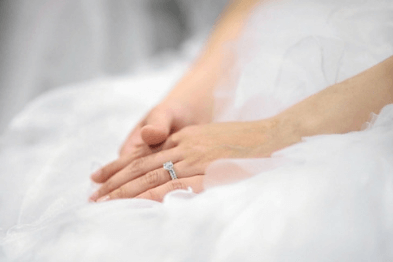 A bride to be wearing a diamond and white gold engagement ring