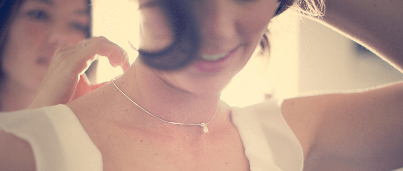 Young bride smiling as she puts on a diamond necklace